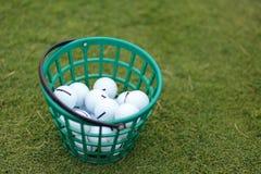 Шары для игры в гольф в корзине на предпосылке травы Стоковая Фотография RF