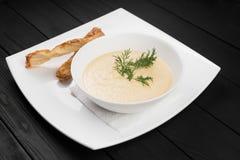 Шар белого cream супа на черной деревянной предпосылке Стоковая Фотография RF