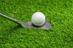 Шар для игры в гольф и гольф-клуб на траве стоковое изображение