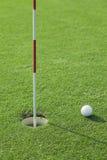 Шар для игры в гольф и одно отверстие на зеленом цвете Стоковые Изображения RF