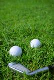 Шар для игры в гольф и тройник на предпосылке курса гольфа зеленой стоковые фотографии rf