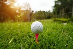 Шар для игры в гольф на тройнике в красивом поле для гольфа на предпосылке захода солнца стоковые изображения rf