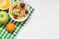 Шар здорового салата свежих фруктов на белой деревянной предпосылке, взгляде сверху, космосе экземпляра стоковое изображение