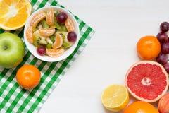 Шар здорового салата свежих фруктов на белой деревянной предпосылке, взгляде сверху, космосе экземпляра стоковое фото rf
