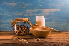Шар и бутылка хлопьев на деревянном столе Стоковые Изображения