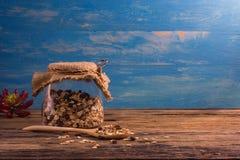 Шар и бутылка хлопьев на деревянном столе Стоковые Фотографии RF