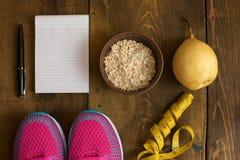 Шар овсяной каши, банана с желтой лентой для измеряя диаграммы, пустого блокнота и тренеров на темной деревянной предпосылке Стоковые Фотографии RF