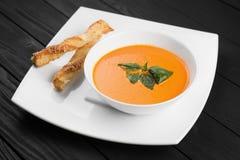 Шар супа сливк моркови на черной деревянной предпосылке Стоковые Изображения