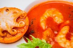 Шар супа томата с креветками с малым осьминогом испек на оранжевом куске конец-вверх, взгляд сверху Стоковые Изображения RF