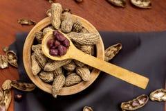 Шар с арахисами с раковиной и, который слезли с ложкой на деревянной поверхности стоковое фото