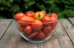 Шар с красными томатами на деревянном столе Стоковые Изображения