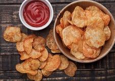 Шар с обломоками хрустящих корочек картошки и кетчуп на деревянной доске Стоковые Фотографии RF