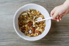 Шар с muesli и ложка на деревянном столе подготовили для здорового завтрака, руки ребенка Стоковые Фото