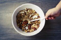 Шар с muesli и ложка на деревянном столе подготовили для здорового завтрака, руки ребенка Стоковая Фотография
