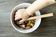 Шар с muesli и ложка на деревянном столе подготовили для здорового завтрака, руки ребенка Стоковое Фото