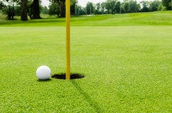 Шар для игры в гольф на губе отверстия на зеленом цвете стоковые изображения
