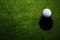 Шар для игры в гольф на зеленой траве сверху стоковое изображение