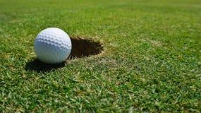 Шар для игры в гольф отверстием стоковое изображение