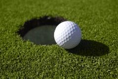 Шар для игры в гольф сидит на крае отверстия Стоковое Изображение RF