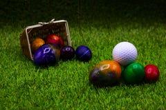 Шар для игры в гольф с пасхальными яйцами на зеленой траве Стоковые Фотографии RF