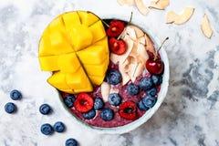 Шар smoothie superfoods завтрака Acai с манго, голубикой, вишней, кокосом шелушится Надземный, взгляд сверху Стоковое Фото
