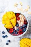 Шар smoothie superfoods завтрака Acai с манго, голубикой, вишней, кокосом шелушится Надземный, взгляд сверху Стоковое Изображение RF