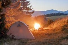 Шатер Hikers в горах на вечере с костром с sparkles Стоковое Изображение