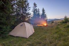 Шатер Hikers в горах на вечере с костром с sparkles Стоковое фото RF