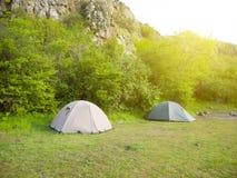 2 шатра стоят в лесе с горами в предпосылке Стоковые Фото