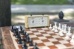 Шахматная доска с частями и часы на деревянном столе в связи с турниром шахмат Турнир шахмат с часами шахмат дальше стоковое изображение