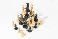Шахматные фигуры на белой предпосылке формируя пирамиду стоковое фото rf