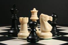 Шахматные фигуры на борту с черной предпосылкой Стоковое Фото