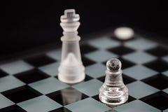 Шахматные фигуры стекла: пешки и король оппозиции на черной предпосылке стоковая фотография rf