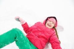 Шаловливая девушка играя в снеге, делая ангела снега Стоковое Фото