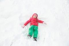 Шаловливая девушка играя в снеге, делая ангела снега Стоковое Изображение