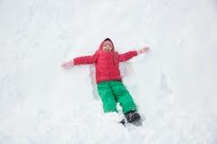 Шаловливая девушка играя в снеге, делая ангела снега Стоковое Изображение RF