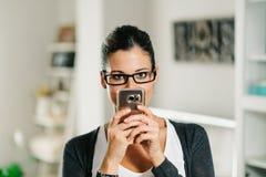 Шаловливая женщина используя smartphone дома Стоковое Изображение RF