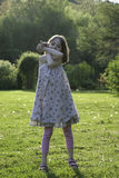 Шаловливая и счастливая маленькая девочка в солнечном саде Стоковые Изображения