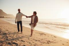 Шаловливые старшие пары на пляже Стоковые Фото