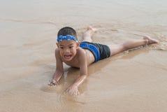 Шаловливый мальчик на пляже с морем на предпосылке. Стоковые Фотографии RF