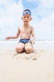 Шаловливый мальчик на пляже с морем на предпосылке. Стоковая Фотография