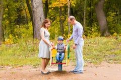 Шаловливый ребенок с родителями на спортивной площадке внешней Мама, папа и ребенк стоковые изображения rf