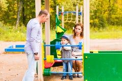 Шаловливый ребенок с родителями на спортивной площадке внешней Мама, папа и ребенк стоковая фотография rf