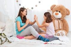 2 шаловливых счастливых сестры сидя и играя совместно Стоковое фото RF