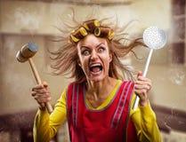 Шальная домохозяйка с инструментами кухни Стоковое фото RF