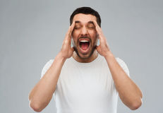 Шальной крича человек в футболке над серой предпосылкой стоковые изображения rf