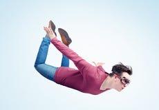 Шальной человек в изумлённых взглядах летает в небо Концепция шлямбура стоковое изображение rf