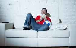 Шальной человек держа деньги и футбольный мяч смотря футбол на пари интернета ТВ онлайн играя в азартные игры Стоковое Изображение
