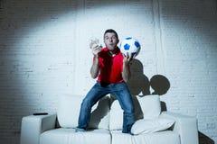 Шальной человек держа деньги и футбольный мяч смотря футбол на пари интернета ТВ онлайн играя в азартные игры Стоковые Фото