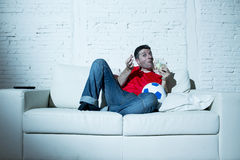 Шальной человек держа деньги и футбольный мяч смотря футбол на пари интернета ТВ онлайн играя в азартные игры стоковая фотография
